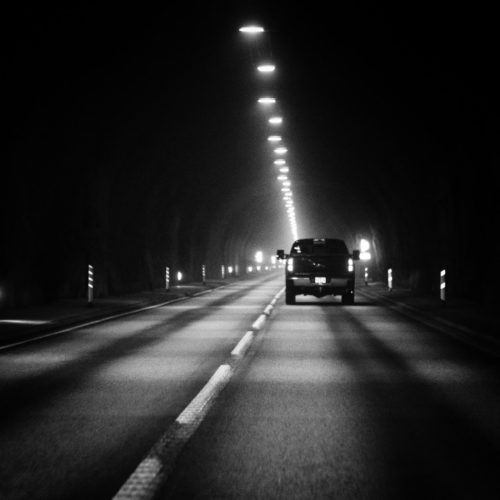 Black and white image of truck driving in a dark tunnel with lights down the middle of the ceiling