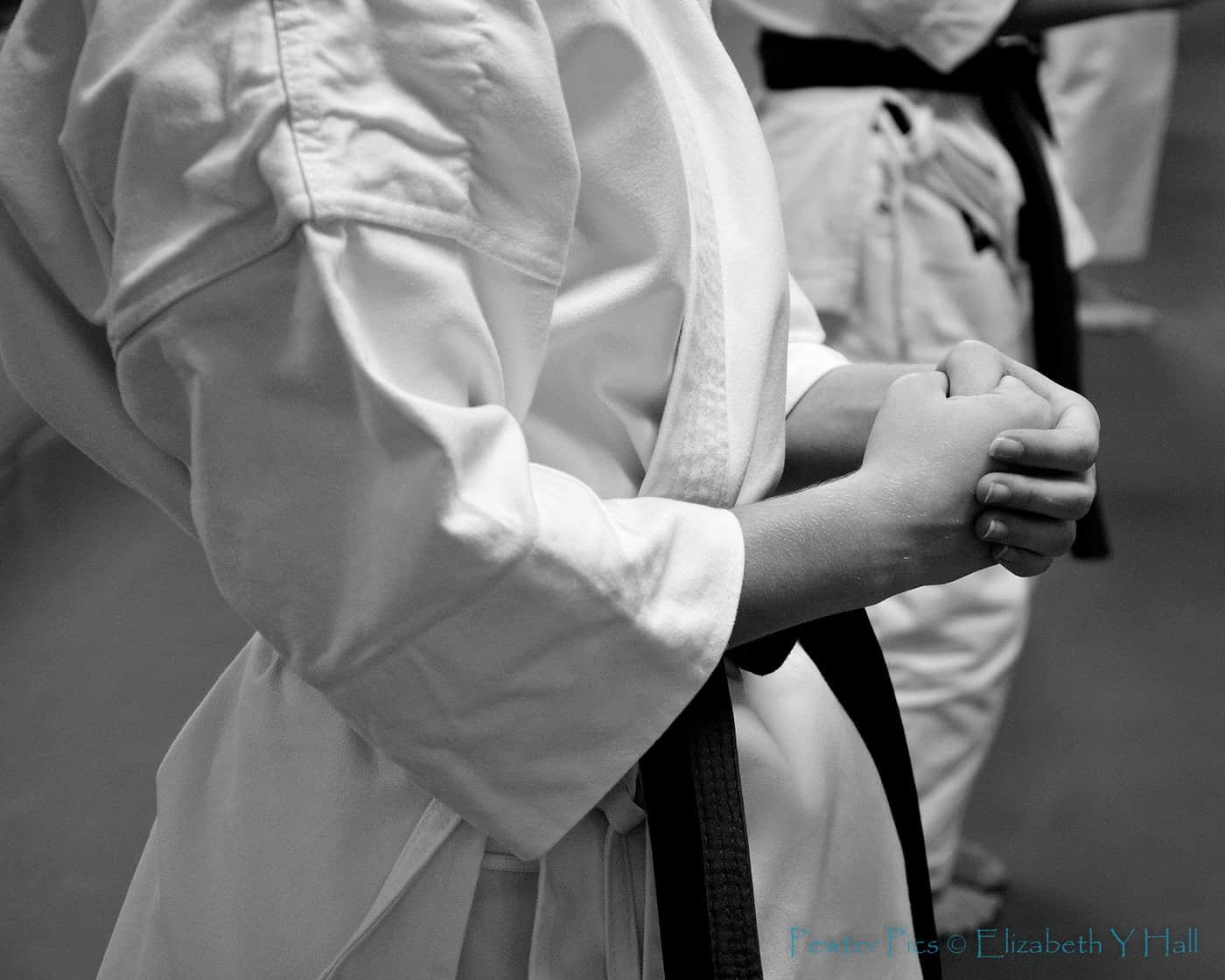 Close up of woman wearing martial arts robe with black belt in karate