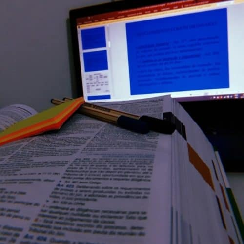 Close up of law school textbook with post it, pen and laptop computer screen in background to show final test anxiety attack