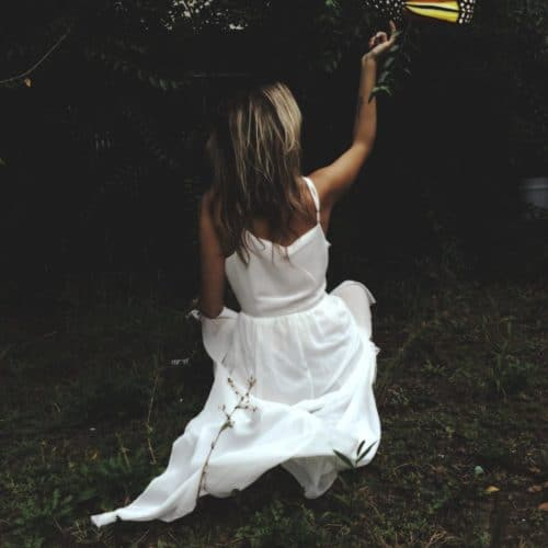 Woman in white dress kneeling in grassy garden stretching her arm to touch a large fantasy butterly
