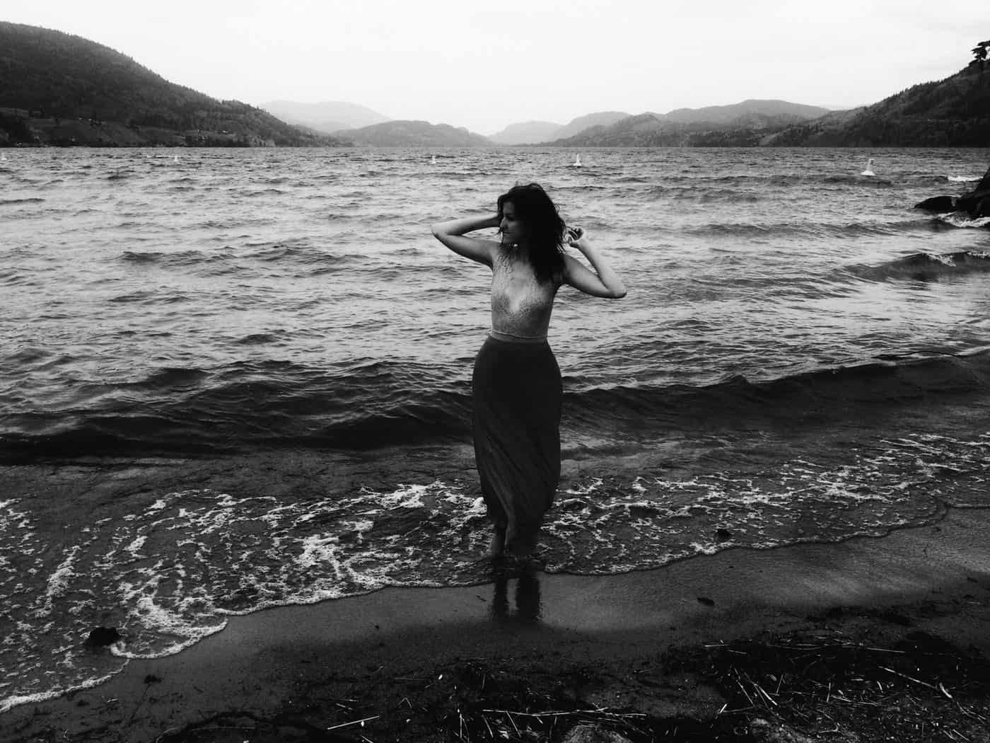 Black and white photo of woman standing beside ocean waves with mountains in the background