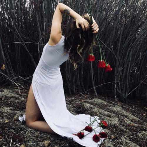 Woman facing away on her knees in white dress with heads on her head and roses in her hands and on ground with bare trees and ground