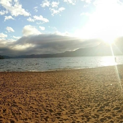 Wide photo of beach and ocean with clouds and mountains in the background along with bright sunflare
