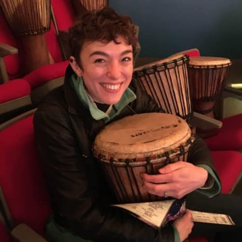 Smiling young woman holding a bongo drum in theatre seats with drums all around