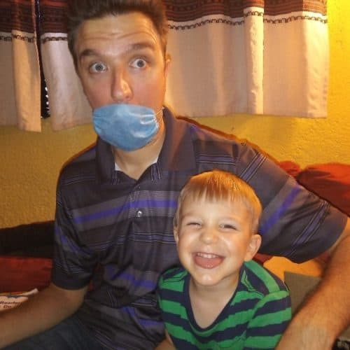 Photo of man wearing medical mask sitting on couch with young son smiling