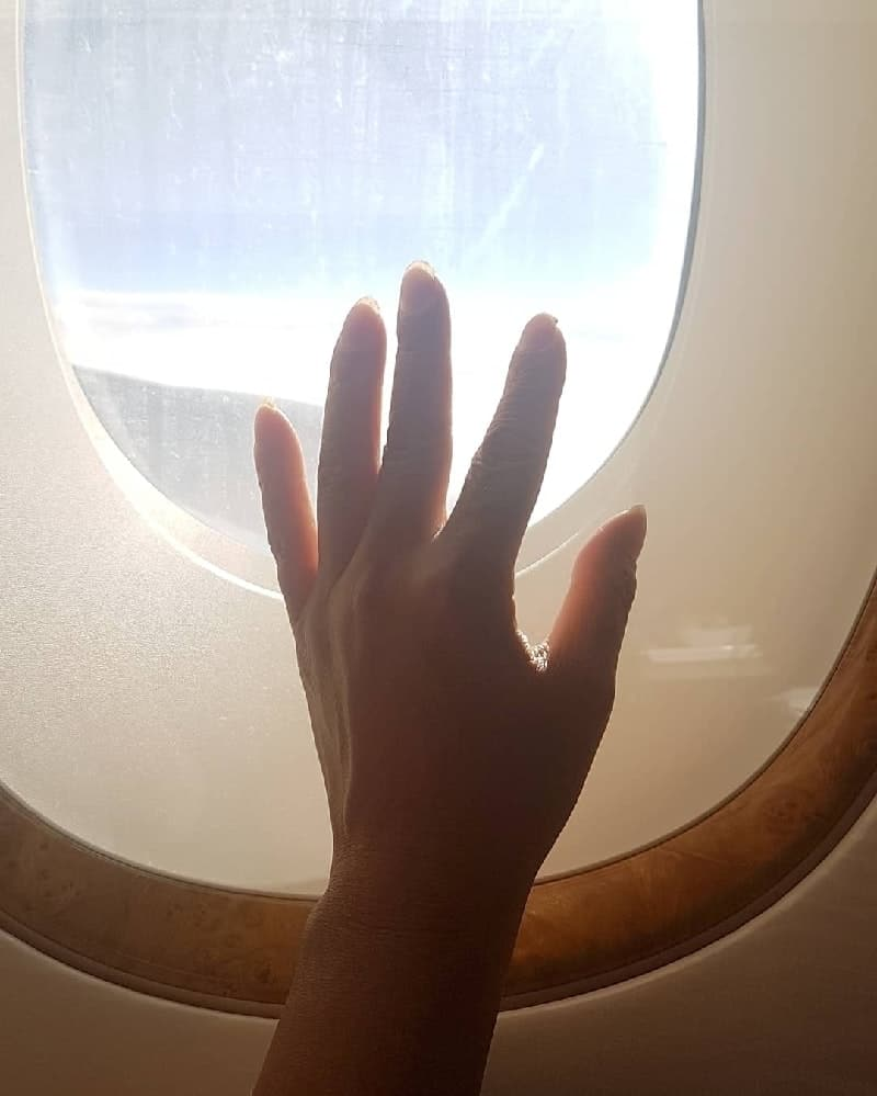 Hand placed on window of airplane with light shining though
