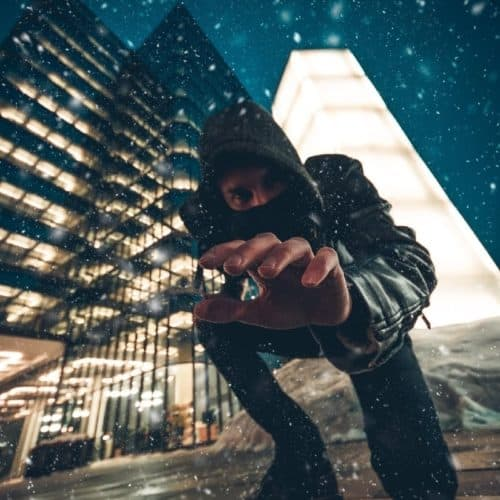 Young man with hood and mask reaching down at viewer with city, snow, night sky and building in the background
