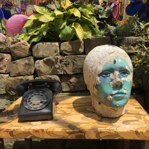 Wooden table with old rotary telephone and statue head with paint peeling off