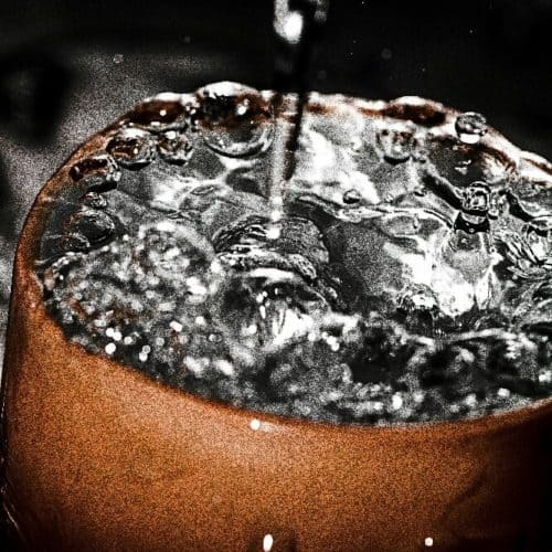 Grainy and high contrast photo of water dripping into overflowing mug