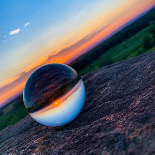 Glass orb on rock refracting the light of a colourful sunset